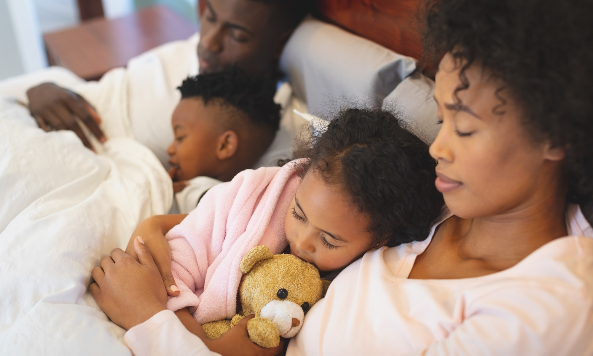 Close-up of African American family sleeping together on bed in bedroom at home