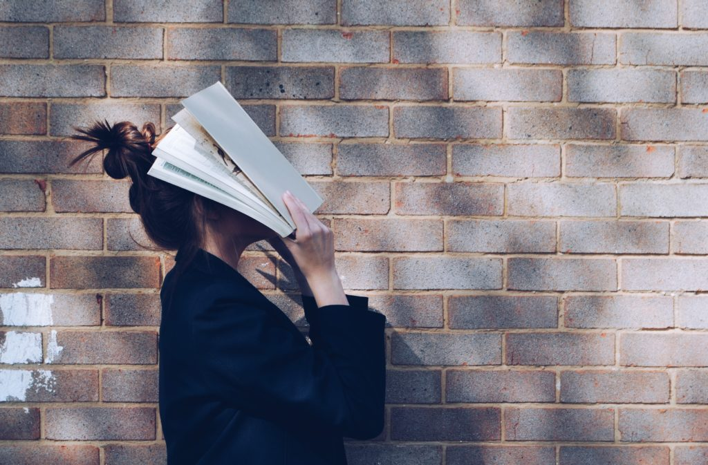 A stressed out student holds a book over her face.